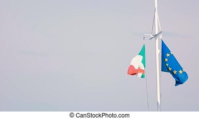 Flags of EU and Italy. Flags waving in the wind. Democratic...