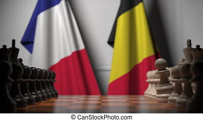 Flags of France and Belgium behind pawns on the chessboard. Chess game or political rivalry related 3D animation