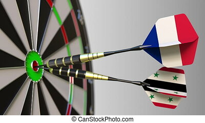 Flags of France and Syria on darts hitting bullseye of the...