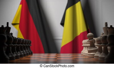 Flags of Germany and Belgium behind pawns on the chessboard. Chess game or political rivalry related 3D animation