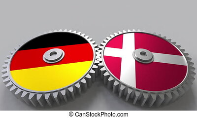 Flags of Germany and Denmark on meshing gears. International...
