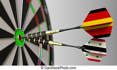 Flags of Germany and Syria on darts hitting bullseye of the...