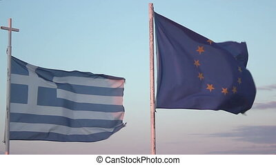 """Flags of Greece and EU waving in wind against blue sky..."