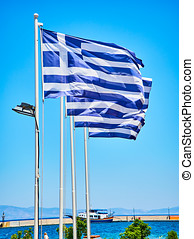 Flags of Greece waving on a blue sky.