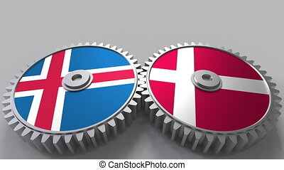 Flags of Iceland and Denmark on meshing gears. International...