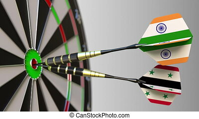 Flags of India and Syria on darts hitting bullseye of the...