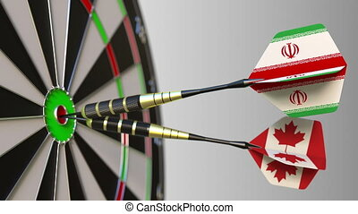 Flags of Iran and Canada on darts hitting bullseye of the target. International cooperation or competition animation