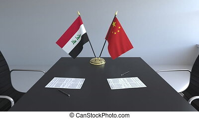 Flags of Iraq and China and papers on the table....