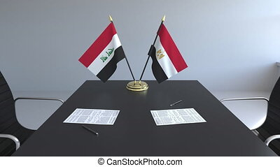 Flags of Iraq and Egypt and papers on the table....