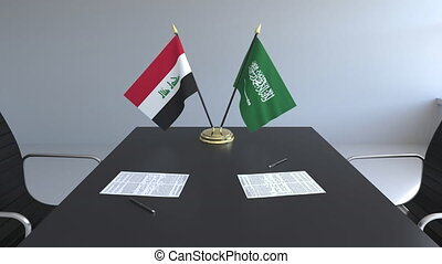 Flags of Iraq and Saudi Arabia and papers on the table....
