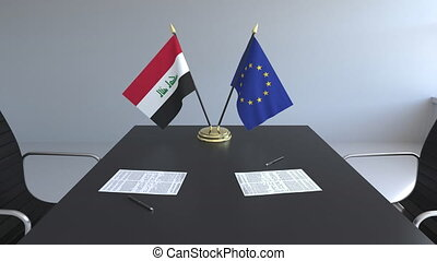 Flags of Iraq and the European Union and papers on the...
