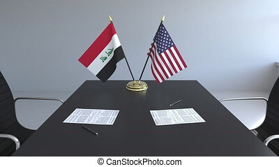Flags of Iraq and the United States and papers on the table....