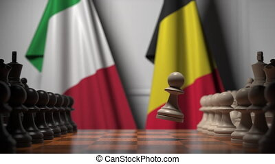Flags of Italy and Belgium behind pawns on the chessboard. Chess game or political rivalry related 3D animation