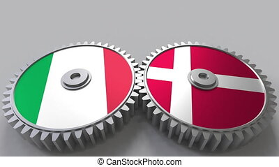 Flags of Italy and Denmark on meshing gears. International...