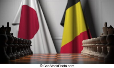Flags of Japan and Belgium behind pawns on the chessboard. Chess game or political rivalry related 3D animation