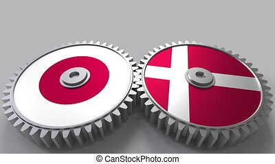 Flags of Japan and Denmark on meshing gears. International...