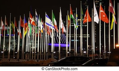 flags of many countries flutter on flagstaffs against houses...