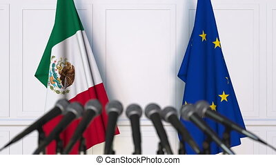 Flags of Mexico and the European Union at international meeting or negotiations press conference