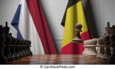 Flags of Netherlands and Belgium behind pawns on the chessboard. Chess game or political rivalry related 3D animation