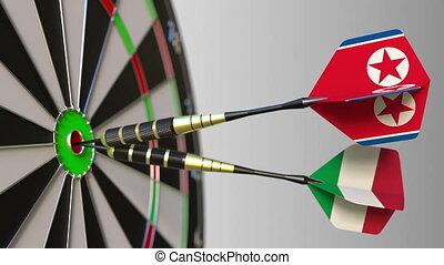 Flags of North Korea and Italy on darts hitting bullseye of...