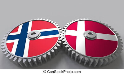 Flags of Norway and Denmark on meshing gears. International...