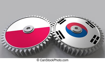 Flags of Poland and Korea on meshing gears. International...