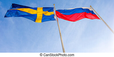 Flags of Russia and Sweden waving against blue sky