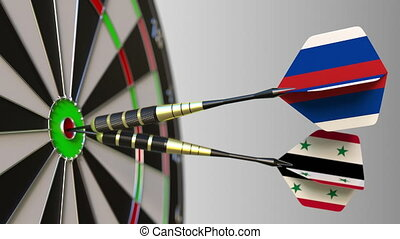Flags of Russia and Syria on darts hitting bullseye of the...