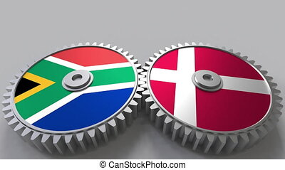 Flags of South Africa and Denmark on meshing gears....