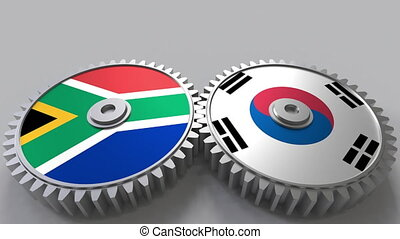 Flags of South Africa and Korea on meshing gears....