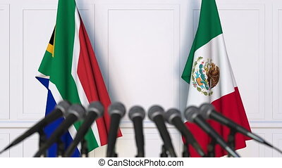 Flags of South Africa and Mexico at international meeting or...