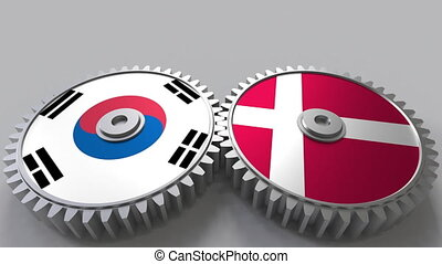 Flags of South Korea and Denmark on meshing gears....