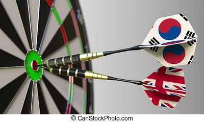 Flags of South Korea and the United Kingdom on darts hitting...