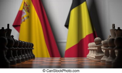 Flags of Spain and Belgium behind pawns on the chessboard. Chess game or political rivalry related 3D animation