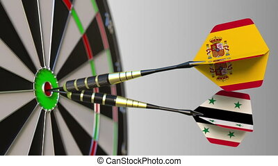 Flags of Spain and Syria on darts hitting bullseye of the...