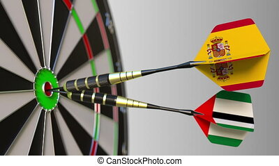 Flags of Spain and the UAE on darts hitting bullseye of the...