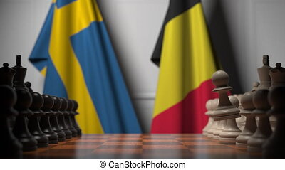 Flags of Sweden and Belgium behind pawns on the chessboard. Chess game or political rivalry related 3D animation