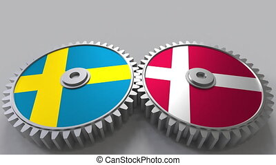 Flags of Sweden and Denmark on meshing gears. International...