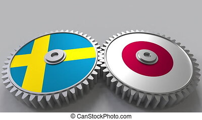 Flags of Sweden and Japan on meshing gears. International...