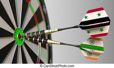 Flags of Syria and India on darts hitting bullseye of the...