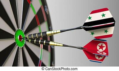 Flags of Syria and North Korea on darts hitting bullseye of...
