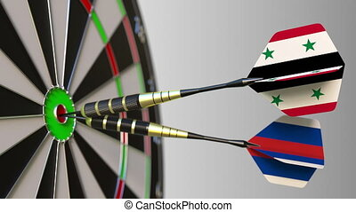 Flags of Syria and Russia on darts hitting bullseye of the...