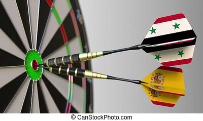 Flags of Syria and Spain on darts hitting bullseye of the...