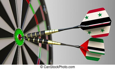 Flags of Syria and the UAE on darts hitting bullseye of the...