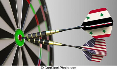 Flags of Syria and the USA on darts hitting bullseye of the...