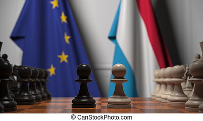 Flags of the EU and Luxembourg behind chess board. The first...