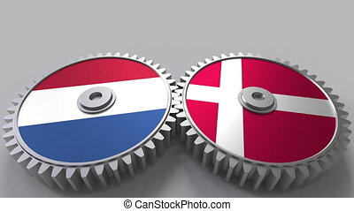 Flags of the Netherlands and Denmark on meshing gears....