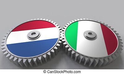 Flags of the Netherlands and Italy on meshing gears....