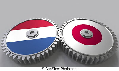 Flags of the Netherlands and Japan on meshing gears....