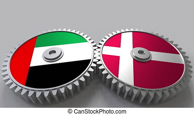Flags of the UAE and Denmark on meshing gears. International...